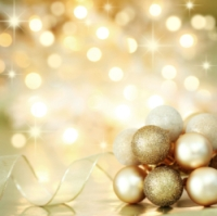 Gold Christmas baubles and ribbon on background of defocused golden lights. Shallow DOF.
